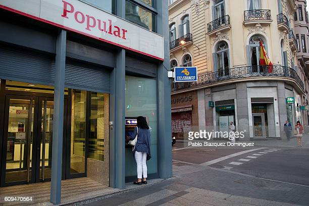 A woman uses a cash machine at a Banco Popular branch on September 21 2016 in Madrid Spain Spain's Banco Popular plans to cut around 3000 jobs and...