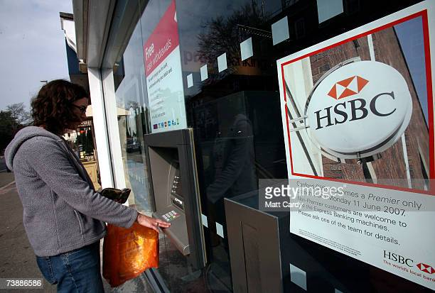 A woman uses a cash machine outside the branch of HSBC in Canford Cliff on April 14 2007 in Poole Dorset The area has some of the most expensive and...