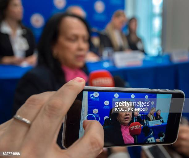 A woman uses a cell phone to record Interim Representative of Venezuela at the Organization of American States Carmen Luisa Velasquez after she burst...