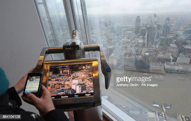 A woman uses a digital telescope at The View at the Shard building in London which was opened to the public today