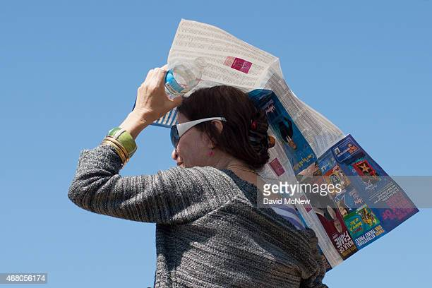 A woman uses a Hollywood tourist map as a makeshift sunshade in Griffith Park on March 29 2015 in Los Angeles California A recordbreaking series of...