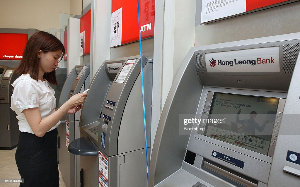 A woman uses a Hong Leong Bank Bhd. automated teller machine (ATM) in Kuala Lumpur, Malaysia, on Wednesday, Feb. 27, 2013. Hong Leong Bank, the Malaysian lender controlled by billionaire Quek Leng Chan, plans to boost profit from overseas to as much as 20 percent of earnings as trade in Southeast Asia grows and emerging markets recover. Photographer: Goh Seng Chong/Bloomberg via Getty Images