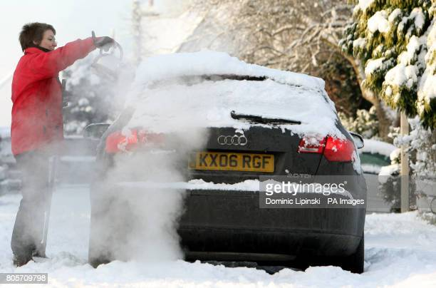 A woman uses a kettle to melt ice from a parked car in Benson Oxfordshire which recorded a low of minus 177 degrees centigrade overnight