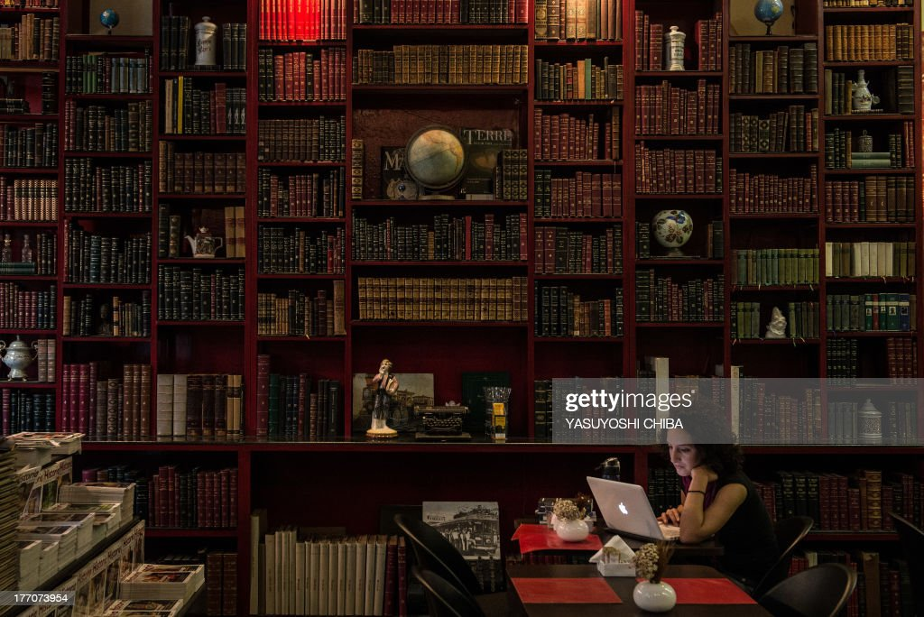 A woman uses a laptop computer at a cafe inside a bookstore in downtown Rio de Janeiro, Brazil on August 20, 2013. The bookstore specializes in second hand books written in Portuguese or French published in the19th and 20th centuries. The oldest book is a religious one written in Hebrew and published in 1750.
