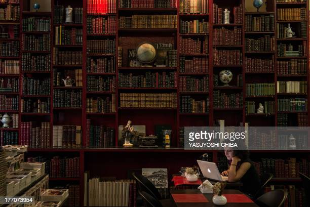 A woman uses a laptop computer at a cafe inside a bookstore in downtown Rio de Janeiro Brazil on August 20 2013 The bookstore specializes in second...