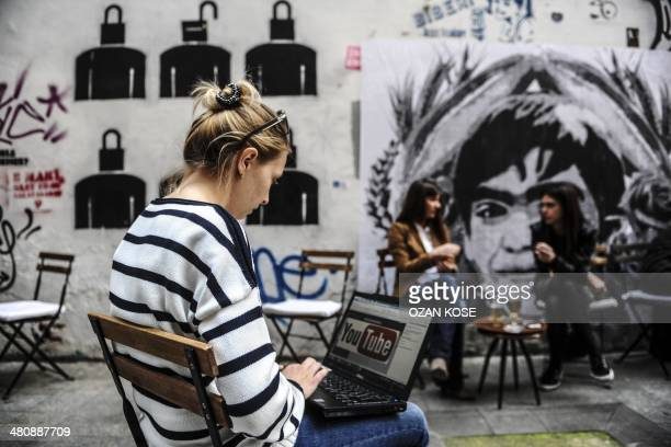 A woman uses a laptop computer showing Youtube's logo on March 27 2014 in Istanbul near a poster Berkin Elvan the 15yearold boy who died nine months...