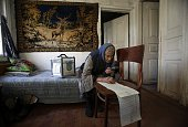 A woman uses a magnifying glass to read her ballot while voting at home in the village of Gornostaypol some 80 km north of Kiev on October 26 during...