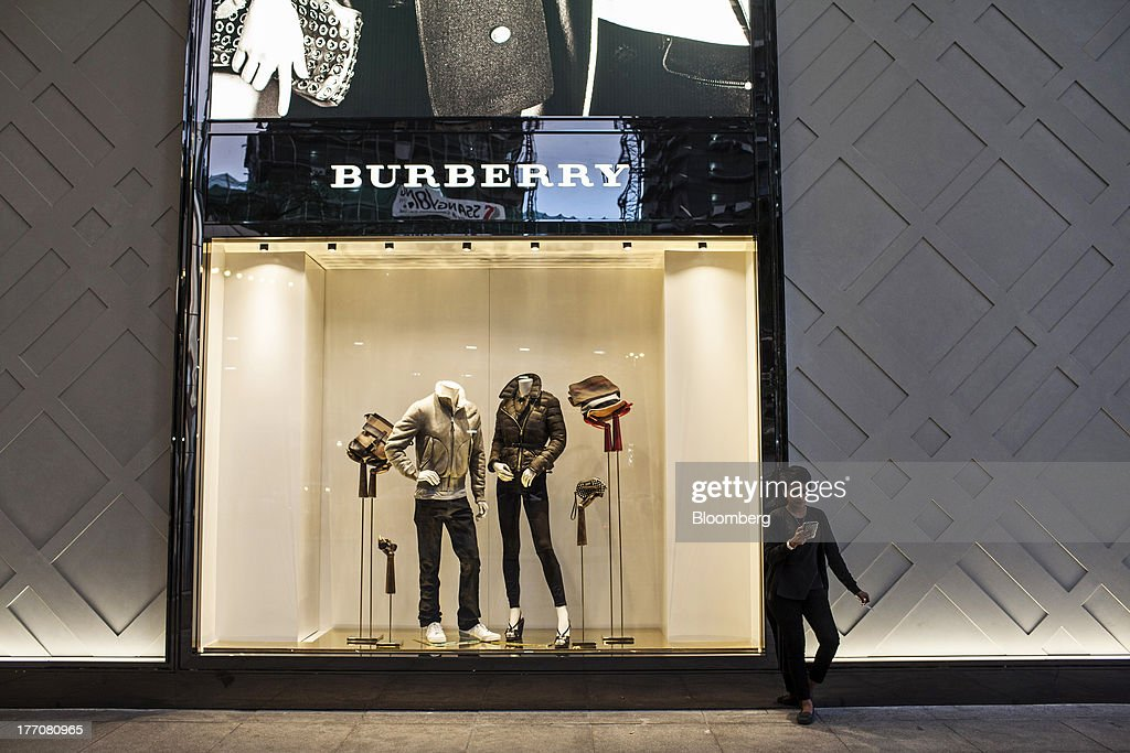 A woman uses a mobile device and smokes a cigarette beside a Burberry Group Plc window display outside the Petronas Twin Towers (KLCC) in Kuala Lumpur, Malaysia, on Tuesday, Aug. 20, 2013. Malaysia's second-quarter gross domestic product figures are scheduled to be released on Aug. 21. Photographer: Sanjit Das/Bloomberg via Getty Images