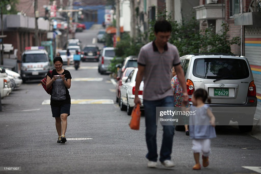 A woman uses a mobile device as she walks down a street behind a man and child in the area of Hannam-dong in Seoul, South Korea, on Wednesday, July 24, 2013. South Koreas economy grew the most in more than two years, on stronger government spending and private consumption even as a slowdown in China clouds the outlook. Photographer: Woohae Cho/Bloomberg via Getty Images