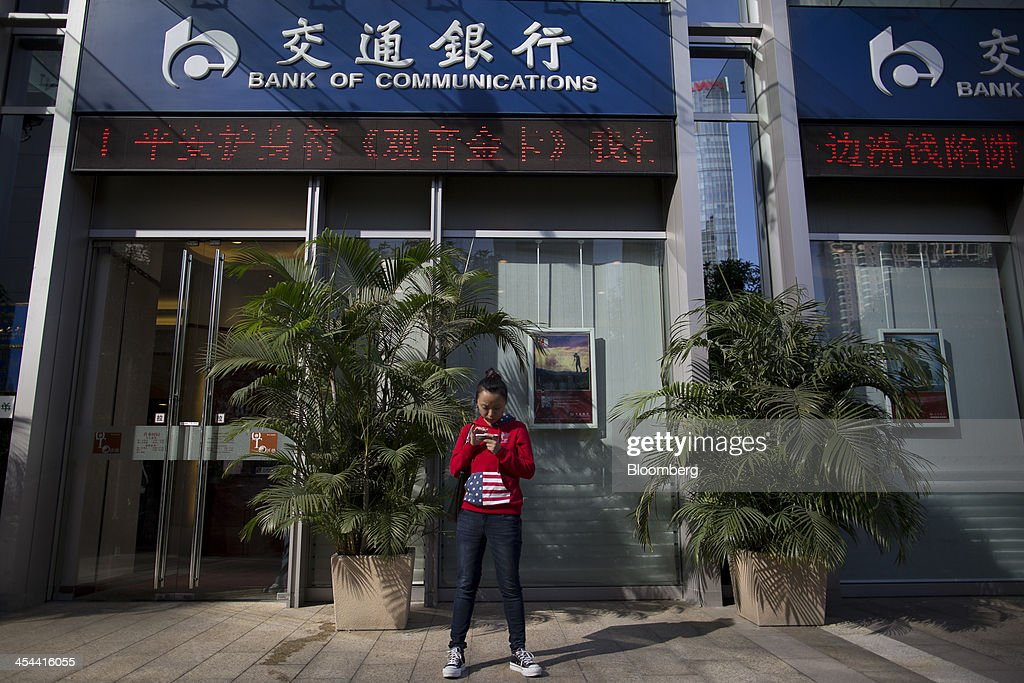 A woman uses a mobile device in front of a Bank of Communications Co. branch in the central business district of Guangzhou, Guangdong province, China, on Monday, Nov. 25, 2013. China's government may set its 2014 growth target at 7 percent, the Economic Information Daily reported on Dec. 3, citing the State Information Center. This compares with a goal of 7.5 percent for this year. Photographer: Brent Lewin/Bloomberg via Getty Images