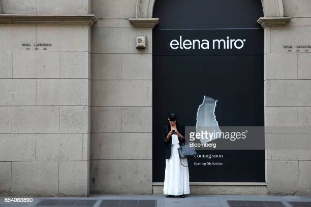 A woman uses a mobile phone as she stands in front of a hoarding advertising a Elena Miro store coming soon in central Milan Italy on Monday Sept 25...