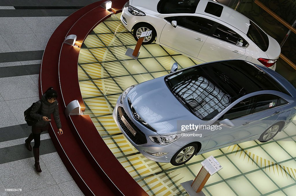 A woman uses a mobile phone as she walks past a Hyundai Motor Co. Sonata hybrid vehicle in the showroom at the company's headquarters in Seoul, South Korea, on Tuesday, Jan. 22, 2013. Hyundai Motor Co. is scheduled to release fourth-quarter earnings on Jan. 24. Photographer: SeongJoon Cho/Bloomberg via Getty Images