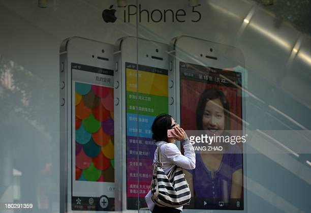A woman uses a mobile phone as she walks past an Apple iPhone 5 poster outside a store in Beijing on September 11 2013 Apple's lowercost iPhone 5C...