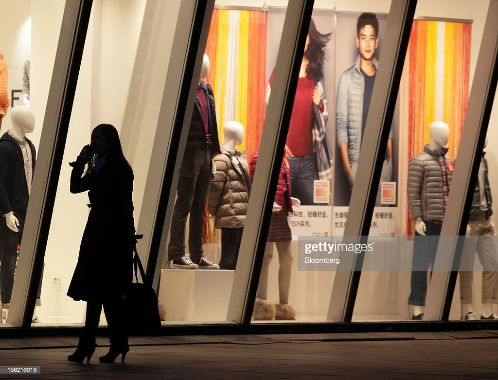 A woman uses a mobile phone as she walks past the windows of a Fast Retailing Co. Uniqlo store in the Sanlitun area of Beijing, China, on Friday, Nov. 9, 2012. China's retail sales exceeded forecasts and inflation unexpectedly cooled to the slowest pace in 33 months, signaling the government is boosting growth without driving a rebound in prices. Photographer: Tomohiro Ohsumi/Bloomberg via Getty Images