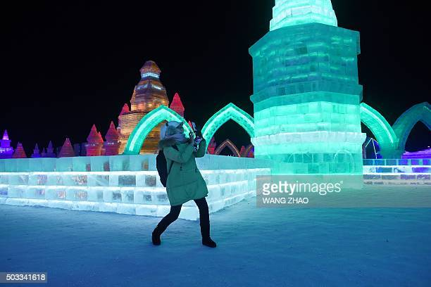 A woman uses a mobile phone to take a picture at the China Ice and Snow World on the eve of the opening ceremony of the Harbin International Ice and...