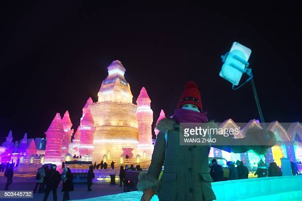 A woman uses a mobile phone to take a picture at the China Ice and Snow World during the Harbin International Ice and Snow Festival in Harbin...
