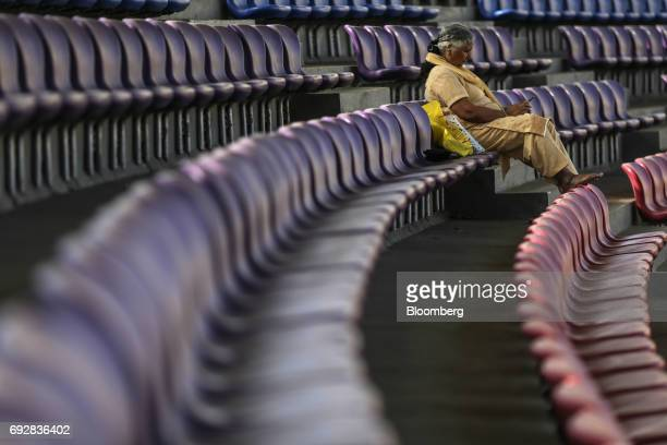 A woman uses a mobile phone while sitting at a cricket stadium in Palava City on the outskirts of Mumbai India on Thursday May 25 2017 Lodha Group...