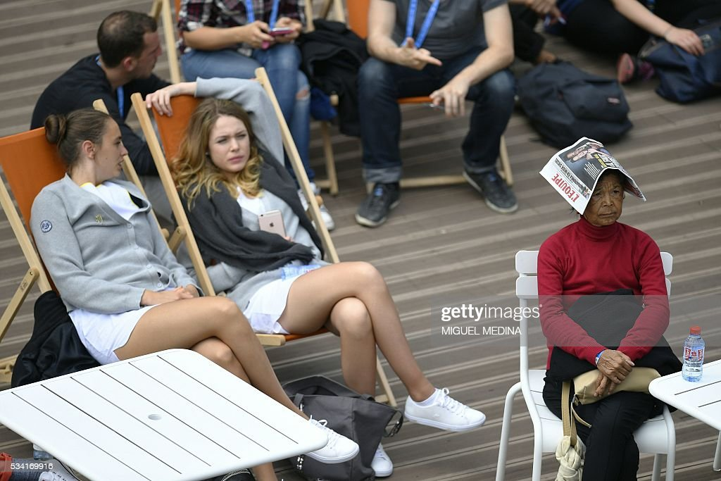 A woman uses a newspaper to cover her head as people sit in deckchairs in the sun in at the Roland Garros 2016 French Tennis Open in Paris on May 25, 2016. / AFP / MIGUEL