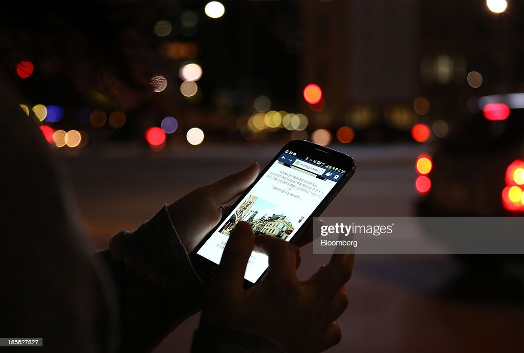 A woman uses a Samsung Electronics Co. Galaxy S4 smartphone at night in Gwanghwamun Square in Seoul, South Korea, on Tuesday, Oct. 22, 2013. Samsung Electronics is scheduled to release third-quarter earnings on Oct. 25. Photographer: SeongJoon Cho/Bloomberg via Getty Images