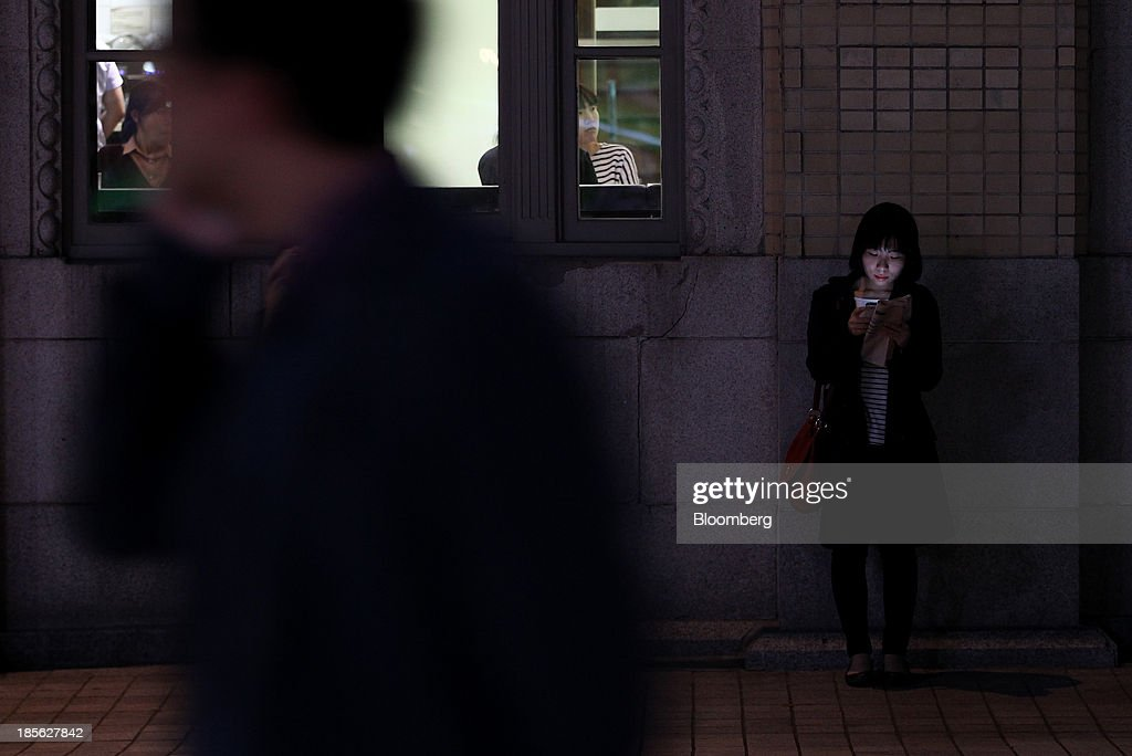 A woman uses a Samsung Electronics Co. Galaxy smartphone at night in Gwanghwamun Square in Seoul, South Korea, on Tuesday, Oct. 22, 2013. Samsung Electronics is scheduled to release third-quarter earnings on Oct. 25. Photographer: SeongJoon Cho/Bloomberg via Getty Images