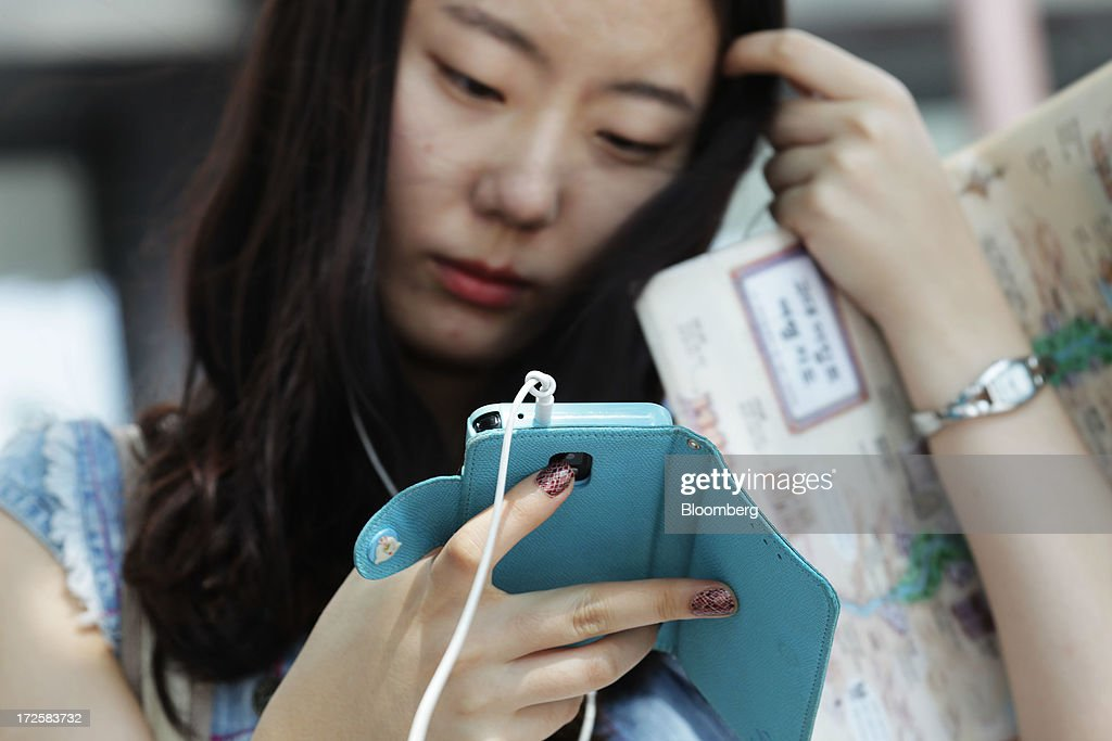 A woman uses a Samsung Electronics Co. smartphone at Gwanghwamun Square in Seoul, South Korea, on Wednesday, July 3, 2013. Samsung Electronics lost $25.3 billion in market capitalization last month, more than the value of competitor Sony Corp., as sales of its flagship Galaxy S4 smartphone fell short of investor expectations. Photographer: Woohae Cho/Bloomberg via Getty Images