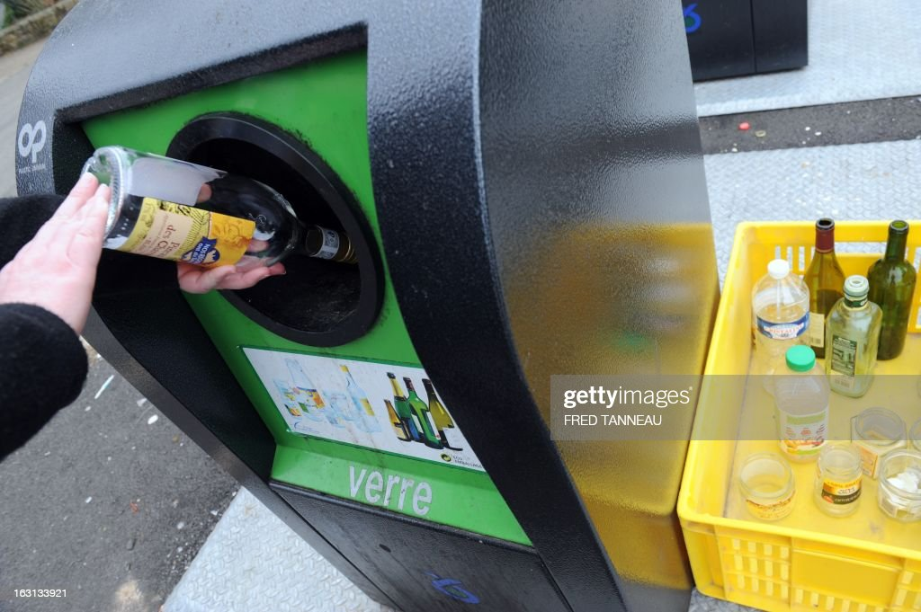 A woman uses a selectif sorting trash container to recycle a glass bottle in Fouesnant, western France on March 5, 2013.
