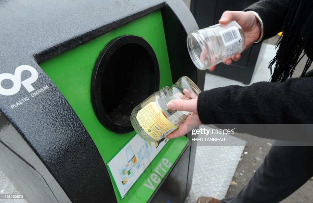 A woman uses a selectif sorting trash container to recycle a glass jars in Fouesnant, western France on March 5, 2013.