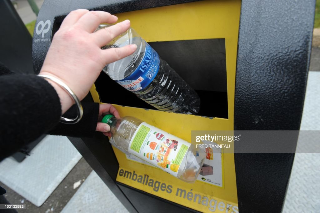 A woman uses a selectif sorting trash container to recycle a plastic bottle in Fouesnant, western France on March 5, 2013. AFP PHOTO / FRED TANNEAU