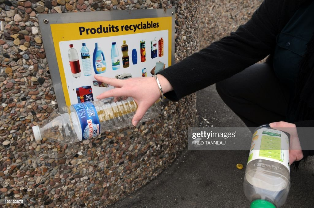 A woman uses a selectif sorting trash container to recycle plastic bottles in Fouesnant, western France on March 5, 2013. AFP PHOTO / FRED TANNEAU
