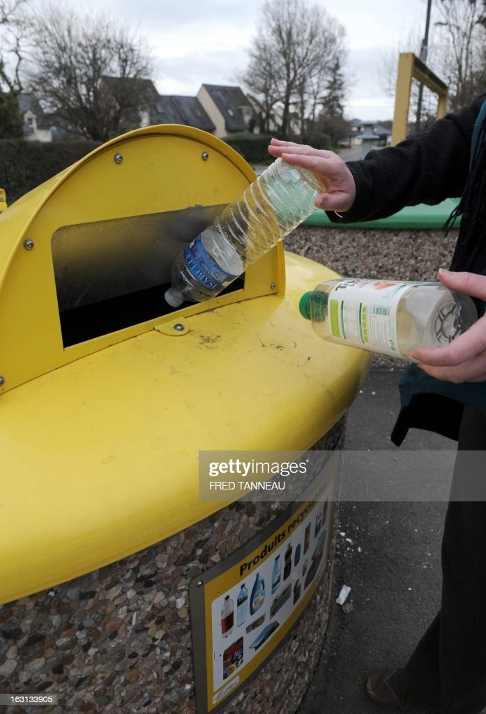A woman uses a selectif sorting trash container to recycle plastic bottles in Fouesnant, western France on March 5, 2013.