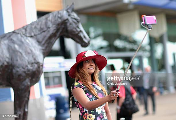 A woman uses a selfie stick to take a photograph on Ladies Day on day 3 of Royal Ascot at Ascot Racecourse on June 18 2015 in Ascot England