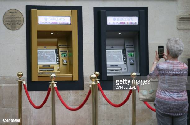 A woman uses a smart phone to take a photograph of a gold coloured automated teller machine installed at a branch of British bank Barclays in Enfield...
