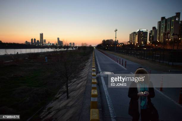 A woman uses a smartphone before the city skyline in Seoul at dusk on March 21 2014 South Korea already one of the most wired countries on earth...