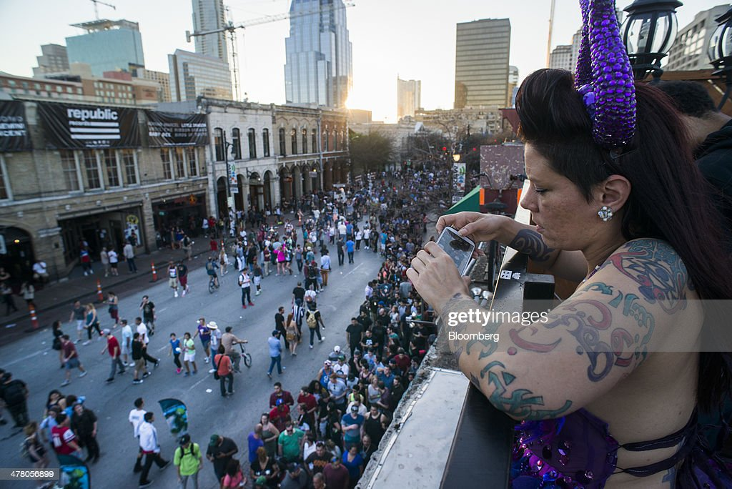 A woman uses a smartphone to take a photograph of pedestrians on 6th Street during the South By Southwest (SXSW) Interactive Festival in Austin, Texas, U.S., on Tuesday, March 11, 2014. The SXSW conferences and festivals converge original music, independent films, and emerging technologies while fostering creative and professional growth. Photographer: David Paul Morris/Bloomberg via Getty Images