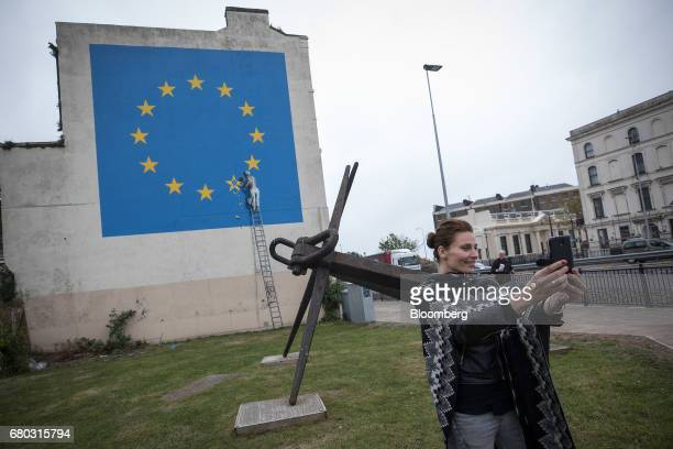 A woman uses a smartphone to take a selfie photograph with a mural depicting a European Union flag being chiseled by a workman on the side of a...