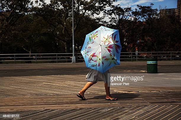A woman uses a sun umbrella along the boardwalk at Brighton Beach in Brooklyn on August 20 2015 in New York City The National Oceanic and Atmospheric...