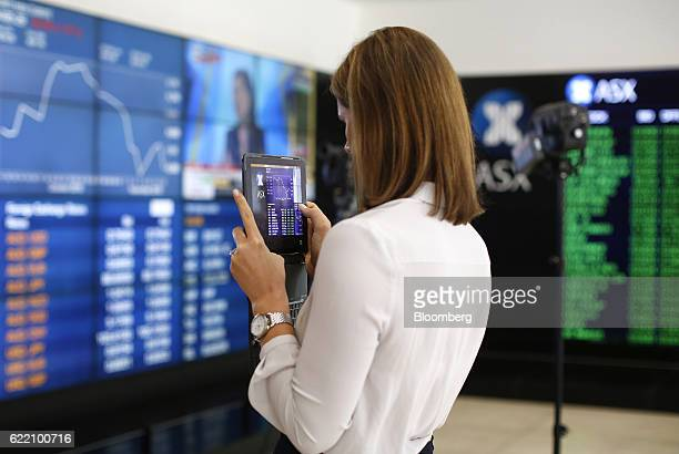 A woman uses a tablet device to take a photograph of an electronic board displaying stock information inside the Australian Securities Exchange...