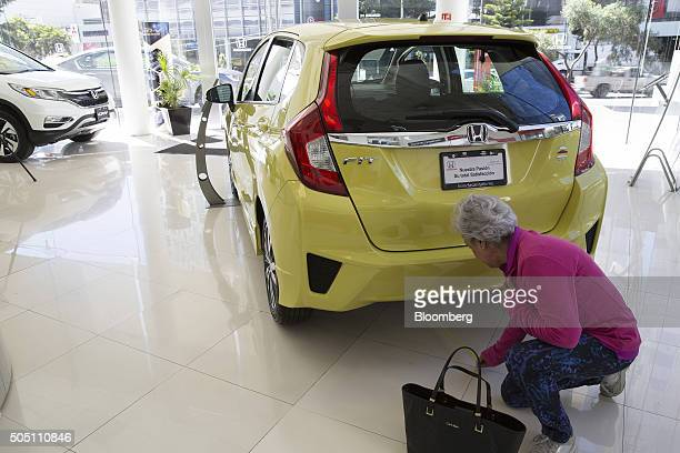 A woman uses a tape measure to determine if a Honda Motor Co Fit model car will fit in her garage at an auto dealership in the Santa Fe neighborhood...