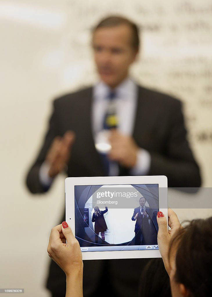 A woman uses an Apple In.c iPad to take a photograph of Marc Bolland, chief executive officer of Marks & Spencer Group Plc, in the hall between sessions on the opening day of the World Economic Forum (WEF) in Davos, Switzerland, on Wednesday, Jan. 23, 2013. World leaders, Influential executives, bankers and policy makers attend the 43rd annual meeting of the World Economic Forum in Davos, the five day event runs from Jan. 23-27. Photographer: Jason Alden/Bloomberg via Getty Images