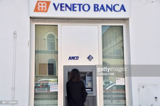 A woman uses an ATM at a branch of Italian bank 'Veneto Banca' in Rome on June 26 2017 Up to 3900 voluntary redundancies and 600 branch closures are...