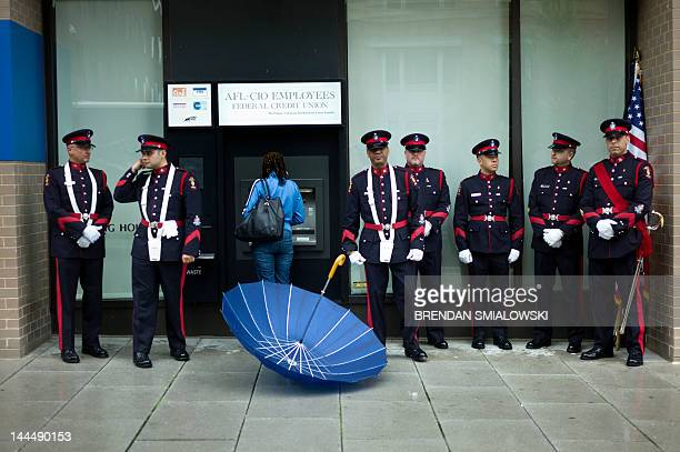 A woman uses an ATM while members of the Peel Regional Police from Ontario Canada wait to march May 14 2012 in Washington DC Police and emergency...