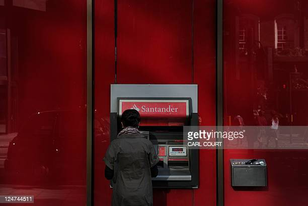 A woman uses an automatic cash machine at a branch of Santander bank in central London on September 12 2011 AFP PHOTO / CARL COURT