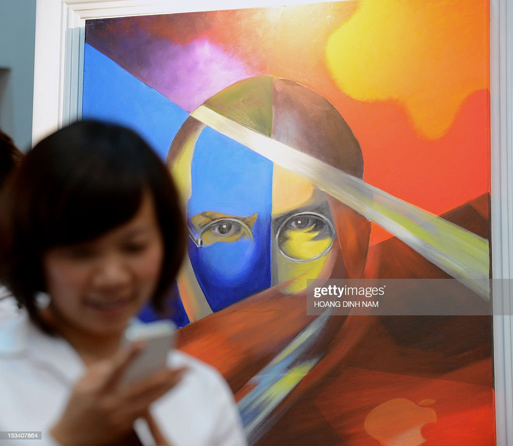 A woman uses an Iphone next to a portrait of Steve Jobs at an art exhibition in commemoration of the late Apple's co-founder Steve Jobs on the occasion of his first death anniversary in Hanoi on October 5, 2012. The art exhibition entitled 'Think Different' was ininiative of a group of local artists and sponsored by the US embassy and Vietnam's National Library. AFP PHOTO/HOANG DINH Nam