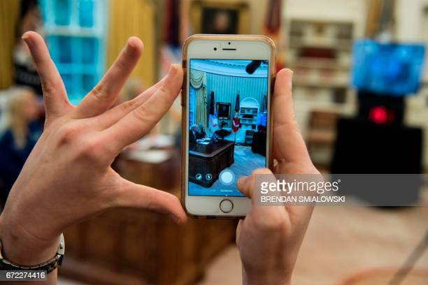 A woman uses an iPhone to take a SnapChat as US President Donald Trump speaks via video with NASA astronauts aboard the International Space Station...