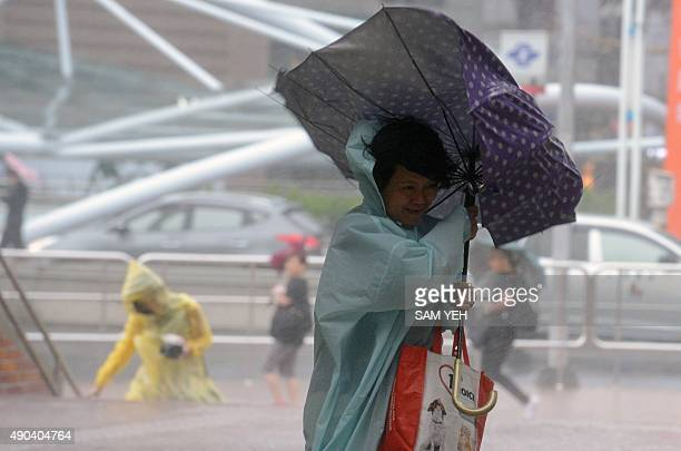 A woman uses an umbrella against strong wind and rain brought by typhoon Dujuan at Tamshui district New Taipei City on September 28 2015 More than...