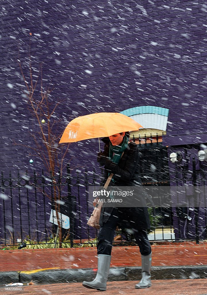 A woman uses an umbrella as she cross a street during a snow storm in Washington, DC, on March 6, 2013. A massive winter storm pounding the northern US on March 6, grounded 2,600 flights, closed hundreds of schools and made roadways and highways impassible. At least four people were reportedly killed in accidents on icy and snow covered roads and highways. AFP PHOTO/Jewel Samad
