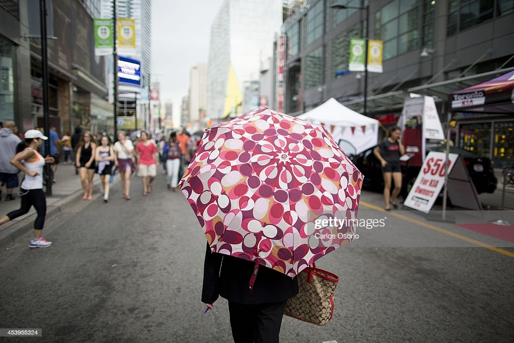 TORONTO, ON - AUGUST 21 - A woman uses an umbrella during the 2014 Scotiabank Busker Festival on August 21, 2014. The festival takes place along Yonge Street from Queen to College and runs until Sunday August 24.