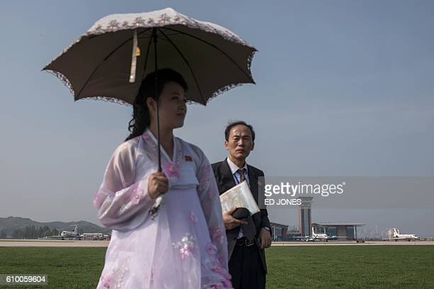 A woman uses an umbrella to shield herself from the sun as she watches a Hughes MD500 helicopter performs a flyby during the first Wonsan Friendship...