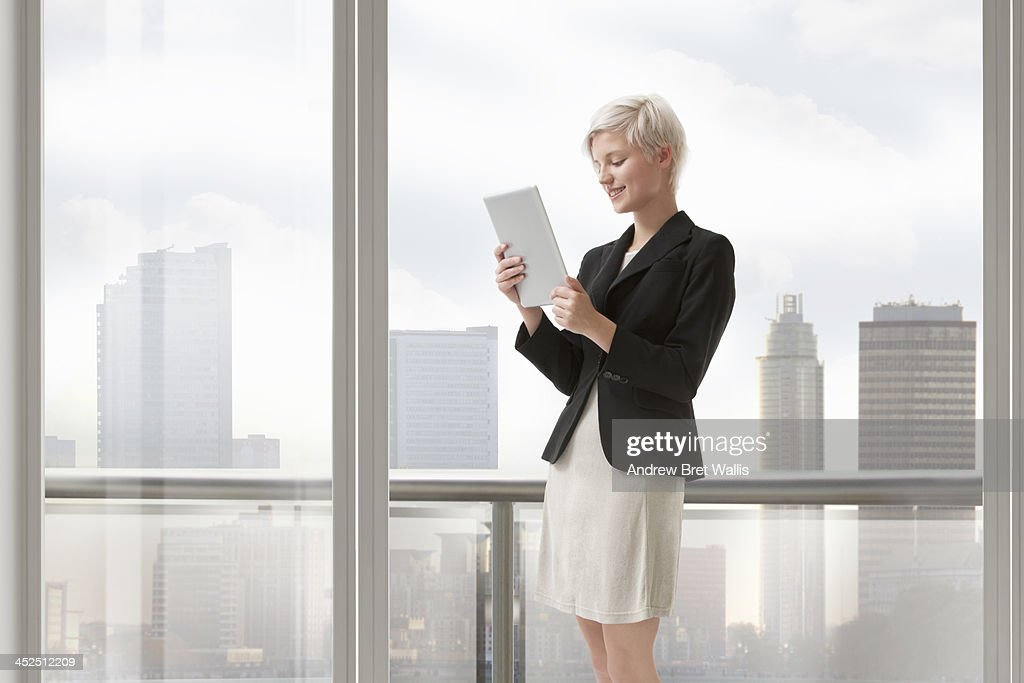 Woman uses computer tablet from apartment balcony : Stock Photo