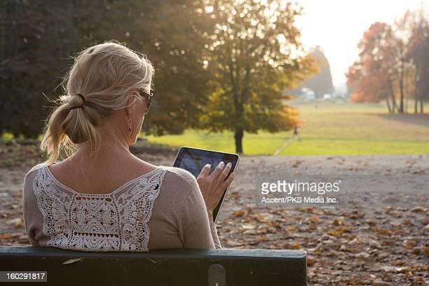 Woman uses digital tablet in urban park, autumn